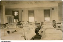 Image of St. Joseph's College infirmary, Rensselaer, Indiana, ca. 1910 - There are about a dozen beds very close to each other, and a wooden chair by each bed.
