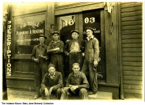 Image of Frank J. Roell Plumbing and Heating office, Indianapolis, Indiana, ca. 1925 - Frank Roell is second from the right in the back row, and is shown with some of his eight sons.
