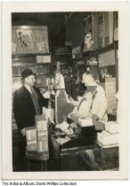 Image of Wilbur Zwickel at his drugstore, Connersville, Indiana, ca. 1945 - Mr. Zwickel is seen helping a customer inside the Economy Drug Store that he ran from 1927 to 1965. Signs are seen for Ipana toothpaste, Bromo Quinine, Modess, Kotex, Teel, and Parke, Davis & Co. products.