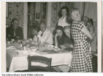 Image of Zwickel family at the dinner table, Connersville, Indiana, ca. 1945 - A woman holds a Dachshund dog while the other view old photographs at the table.