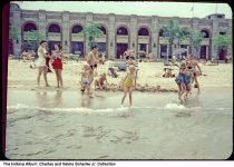 Image of Swimmers by Indiana Dunes pavilion, Chesterton, Indiana, 1954 - Children are seen playing in the water on the beach with adults nearby.