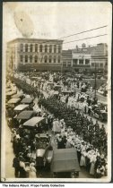 Image of Armistice Day parade by the courthouse, Lafayette, Indiana, ca. 1920 - Men dressed in military are seen marching down the street on the Tippecanoe Courthouse square. The W. H. Zinn Company, Queen City, and The Hub are visible in the background