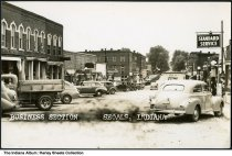 Image of Main Street businesses, Shoals, Indiana, 1941 - Businesses in the 200 and 300 blocks of Main Street from US Highway 50 include a 5 and 10 cent store, Inman's Cafe, the Tip Top cafe, Edwards Soda Fountain, a Shell gas station, and a Standard station.