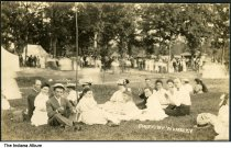 """Image of Group of people at a campground, Camargo, Illinois, ca. 1910 - A group of 15-20 people are seated on the grass in the foreground. In the background are tents among the trees and a large number of other people.   The location of this series of about 39 postcards was not identified; two of the postcards show a building marked """"Patterson Springs,"""" located at the Chautauqua in Patterson Springs, Illinois."""