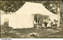 """Image of Group seated under a tent awning, Camargo, Illinois, ca. 1910 - The location of this series of about 39 postcards was not identified; two of the postcards show a building marked """"Patterson Springs,"""" located at the Chautauqua in Patterson Springs, Illinois."""