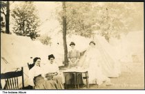 """Image of Four women by a group of tents, Camargo, Illinois, ca. 1910 - The location of this series of about 39 postcards was not identified; two of the postcards show a building marked """"Patterson Springs,"""" located at the Chautauqua in Patterson Springs, Illinois."""