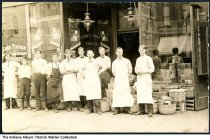 """Image of Employees of Harry Thomas Grocery Store, Indiana, ca. 1910 - Men in work aprons stand in front of a store that reads """"Harry Thomas Grocer"""" on the window. There is a poster for Old Dutch Cleanser in the window, and boxes of Mapl-Flake Cereal stacked inside. Next door on one side is Chester Tucker Watches and Jewelry and Doctor Poling's office at #322 on the other. On the back is handwritten """"Adv. from Pleasant Lake, Ind.,"""" so it may be from the Steuben County area."""