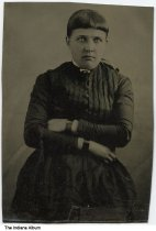 Image of Portrait of Lizzie Hostettler, Indiana, ca. 1865 - This portrait was part of an album of photographs of the Schoonover family of Tippecanoe and Fowler Counties. Her arms are folded across her chest. She may be dressed in mourning clothing, and has shiny black ribbons wrapped around both wrists.