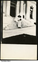 Image of Stylish woman on the steps of a large building, Wabash County, Indiana, ca. 1905 - The building appears to be some sort of government building.