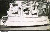 """Image of Parade float passing the Wabash County Courthouse, Wabash, Indiana, ca. 1910 - Two men look out of a large float that holds banners reading """"Service."""""""