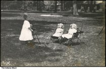 Image of Toddler girl with camera and dolls, Wabash County, Indiana, ca. 1910 - A girls about two years of age stands by a camera on a tripod aimed at two dolls in baby carriages.