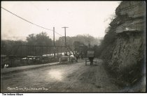 """Image of Horse carriages near a bridge by Southside Park, Wabash, Indiana, ca. 1910 - Two horse carts and a carriage seen by a rocky hill near a bridge. A sign for Simon (?) Cook Co. is seen. The caption reads """"South Side Hill, Wabash, Ind.""""."""