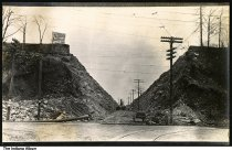 Image of Construction of a cut, Wabash County, Indiana, ca. 1910 - A woman in a fur coat stands in the foreground. A sign for Bockman & Son Shoes is seen at the top of a hill on the left. Workers and wagons are in the background.