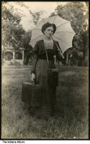 Image of Woman carrying suitcase, parasol, and camera case, Wabash County, Indiana, ca. 1910