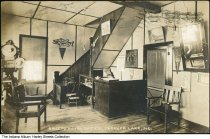 Image of Sheets Hotel office, Angola, Indiana, 1914 - The calendar on the wall appear to read June 1914. The keys to the hotel rooms are on the wall, along with various ads and banners. A typewriter and small cash register are seen.