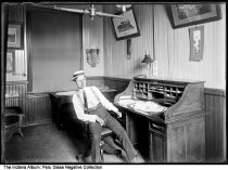 Image of Man in a straw hat at a desk, probably Peru, Indiana, 1904 - Other similar images in this series seem to be of the Wabash Railroad office in Peru, Indiana. Just past the man's left shoulder is a calendar from the Singer sewing machine company that is dated 1904.