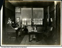 Image of Woman at a desk at the Indiana School for the Deaf, Indianapolis, Indiana, ca. 1923 - Several buildings and grounds of the school can be seen through the window.