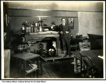 Image of Man with a ledger at the Indiana School for the Deaf, Indianapolis, Indiana, ca. 1923 - The man stands in an office by a desk holding a large ledger.