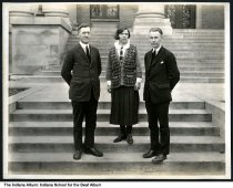 Image of Two men and a woman at the Indiana School for the Deaf, Indianapolis, Indiana, ca. 1923 - The three people are on the front steps of the main building.