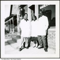 Image of Trio in front of Gaines Barber Shop, Indianapolis, Indiana, ca. 1950 - At one time, the Gaines Barber Shop was owned by Australia Gaines (later Springfield), and was located at 723 (or 732) Indiana Avenue. She may be the woman seen in the center.
