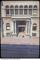 """Image of Birds'-eye view of Indianapolis Public School offices, Indianapolis, Indiana, 1963 - Time stamped July 1963.  Handwritten on the mount is """"School offices from Bd. of Trade (4th). 150 N. Meridian."""" A phone booth is on the left of the entrance."""