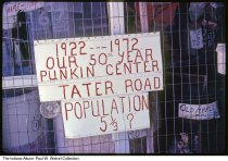 """Image of Sign for Pumpkin Center, Orange County, Indiana, 1972 - Time stamped December, 1972. The sign reads """"1922 - 1972, Our 50th Year - Punkin Center - Tater Road - Population 5 1/3 ?"""""""