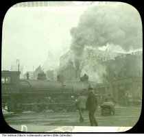 Image of Steam engine passing South Meridian Street, Indianapolis, Indiana, ca. 1912 - Smoke billows from a steam engine on railroad tracks near Union Station. Visible are buildings on the northeast corner of South Meridian and Louisiana Streets, including the Taylor Belting Company at 247 South Meridian and Adams Express Company at 257 South Meridian.
