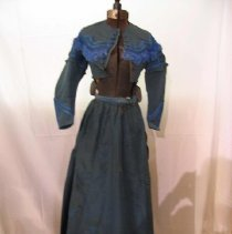 "Image of A bright blue taffeta two piece dress (wedding dress), gathered skirt, fully lined with brown cambric.  Hem faced with narrow blue velvet.  Skirt requires a bustle.  Bodice boned with lighter blue silk flat cord trimming in broad scallops all around top of bodice.  Beyond the two rows of cord, is a 2 1/2"" width fringe in same bright blue.  Sleeves are fitted with top trimmed in a lighter blue.  Flat  cording and ruffle.  The lower rear extends over a bustle which consists of two pieces of taffeta, scalloped and trimmed with silk banding as in other places.  Each loose section has a piece of  silk which turns back over the scalloped part.  Then there are 2 rows of silk bands and fringe on edge.  A huge butterfly type of bow at upper part near the tailored taffeta bow over the ""winged"" bow. - Museum Collection"