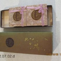Image of Boxed J. B. W. Co. Iridesea Face Powder.  The J. B. Williams Co., Glastonbury, Conn.  USA .  Three cakes of soap in .  Each box is covered with a floral design paper fused to box.  Orchid and gold.  Orchid colored ribbon wraps the box with a bow at lower right end corner.  Inscription on large box  also appears on the individual boxes. - J. B. Williams