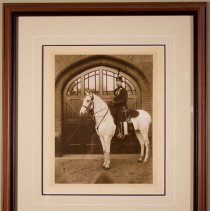 Image of Henry Pellatt  on his horse in front of stables at Casa Loma