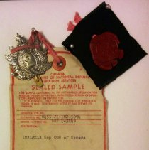 Image of Sealed Sample QOR Cap Badge 1965 with label, seal and swatch - 1965/10/19