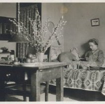 Image of Edith Witmer - Edith in her dorm room. She sits on the bed reading. On the wall hangs a banner and a tennis racket. Nearby, on a table is a vase of pussy willows and other assorted objects. Collection from Penn State College years.