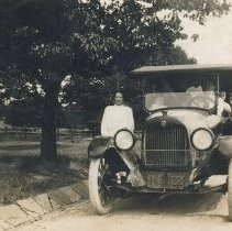 Image of Group - Several people are seated in an auto and a woman and a man stand outside on either side of it. Identified as Jacob Lauver family car (Maxwell) a/b 1922
