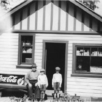 Image of  Moore by store with sons, Tom & Jim - 0108 - Mr Moore with sons Tom and Jim in front of Moore's Grocery Store. 