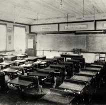Image of Dollarton First School, corner Dollar Rd & Main Hwy - 0124 - Dollarton 1st School, corner Dollar Rd & Main Hwy, SE corner.  Black and White photo of empty classroom, taken from back corner/ door. Rows of desks and writing on chalk board.