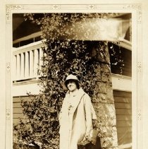 Image of  Mrs Olive Nye, ready to teach at Roche Point - 0130 - Mrs Olive Nye, ready to teach at Roche Point Sepia toned print with frame or woman standing by tree smiling  at camera. She is a long cream coat, holding a briefcase and purse.