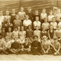 Image of Roche Point School, Class Photo, 1934c. - 0147 - Roche Point School, Class Photo  4 rows of students. With two young women teachers standing on either side. Infront of building with staircase.