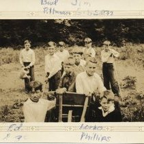 Image of Roche Point School Garden with students, June 1934 - 0149 - Roche Point School garden, ten students, June 1934  Sempia image of students (boys) working in garden.  Three boys sit on wheelbarrel in center.   Image is framed with writing of names/