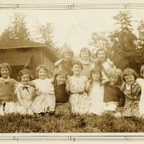 Image of Roche Point Students sitting on lawn  - 0155 - Roche Point 12 students. 13 students sitting on the ground looking at staring and smiling into the camera. School is background.  Framed Sepia