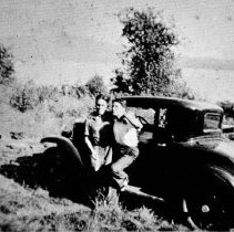 Image of First Nations people and Car on Tsleil - Waututh Nation Land Black and white image of two men leabing on car, looking at camera.