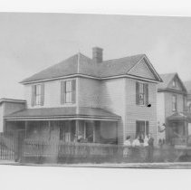 "Image of Clem's House - ""Clem's House,"" with several people standing in the side yard.  The note on the back of the photo identifies the people as MF, Anna, Dorothy, and Clem."