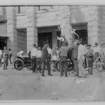 Image of Fire Engine - Unloading Mount Airy's first fire engine in 1916, with a number of people gathered around to watch.   Old First National Bank is in the background.