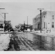 Image of Main Street, Mount Airy - Main Street, Mount Airy, early 1900s.  Post Office is on right, Esso sign on left, and several cars are along the street.  There appears to be snow on the ground.