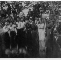 Image of Primitive Baptist Baptism - Primitive Baptist Baptism.  According to information supplied by Mr. Gerry Ackerman, this is a photograph of a Primitive Baptist Baptism which took place during a Camp Meeting around 1920 - 1930.  The location is Brim (now Claudville) Virginia.  Those being baptised are standing in the water, possibly a pond or river, while many others watch from along the bank.
