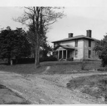 Image of Murlin Sparger House - Murlin Sparger home near Mount Airy, taken from across a dirt road.  In the foreground there is an old automobile, possibly late 1920s to early 1930s.  A rural mailbox stands by the road in front of the house.