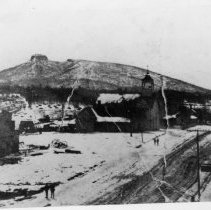 Image of Pilot Mountain - Pilot Mountain, taken from Depot Street.  There is snow on the ground, a church and a few other buildings are in the foreground, and four people can be seen walking along the road.