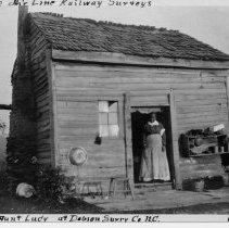 Image of Aunt Lucy's House - Residence of Aunt Lucy.  Information on this picture identifies it as part of the Statesville Railway Surveys.  It shows the small wooden frame residence of Aunt Lucy of Dobson, Surry County, N.C. in October 1907.  The building has a wood shingle roof, various household items on the front porch, and Aunt Lucy is standing in the doorway.