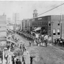 Image of G.C.I.A. Parade - G.C.I.A. Parade, Main Street, Mount Airy.  A small band leads a procession of marchers, onlookers standing along the side of the street.  Business buildings include Hardware and Groceries.
