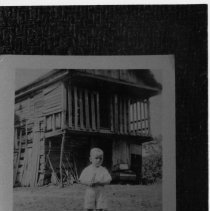 """Image of Boyd or Gilliam Hotel - Boyd or Gilliam Hotel, Shoals.  Young boy standing in front of a delapidated frame building with what appears to be a boarded up second story porch.  Information on the back of the photograph identifies the building as """"Boyd or Gilliam Hotel, Shoals."""""""