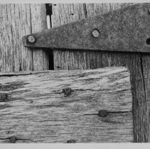 """Image of Door Hinge - Metal door hinge on a log cabin.  Notes on the back of the picture read, """"Album p.1 full page, no margin."""""""